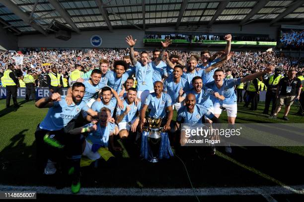 Manchester City players celebrate with the Premier League Trophy after winning the title following the Premier League match between Brighton & Hove...