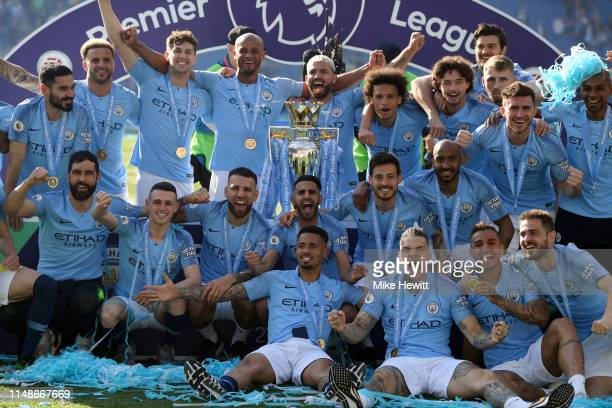 Manchester City players celebrate with the Premier League Trophy after winning the title during the Premier League match between Brighton Hove Albion...
