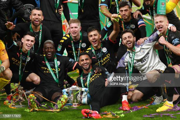 Manchester City players celebrate with the trophy after the Carabao Cup Final match between Aston Villa and Manchester City at Wembley Stadium