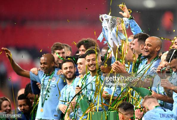 Manchester City players celebrate with the trophy ...