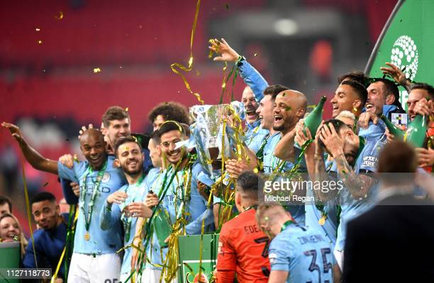 Manchester City players celebrate with the trophy following the Carabao Cup Final between Chelsea and Manchester City at Wembley Stadium on February...