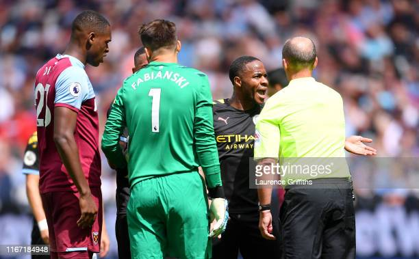 Manchester City players confront referee Mike Dean after a VAR decision leads to their goal being disallowed during the Premier League match between...