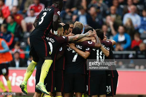 Manchester City players crowd around Manchester City's Argentinian striker Sergio Aguero after he scored their second goal from the penalty spot...