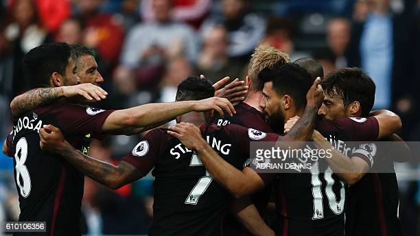Manchester City players crowd Manchester City's Argentinian striker Sergio Aguero to celebrate his second goal during the English Premier League...