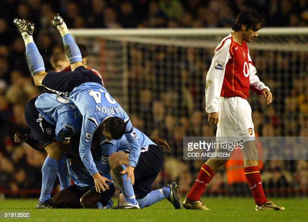 Manchester City players mob Shaun WrightPhillips after scoring against Arsenal as Robert Pires despairs during a premiership match at Highbury in...