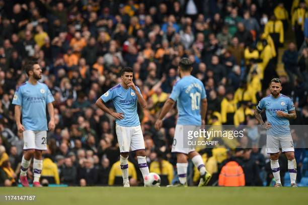 Manchester City players react after conceding their second goal during the English Premier League football match between Manchester City and...