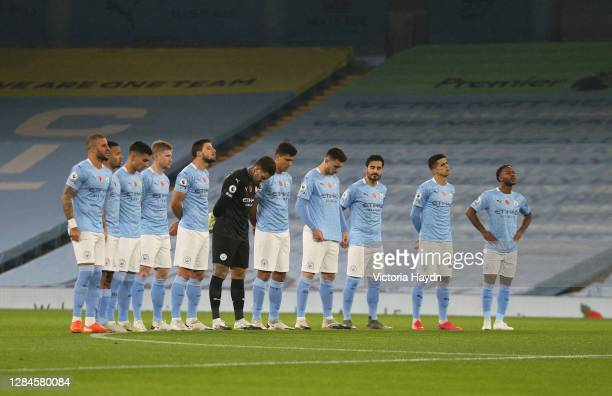 Manchester City players stand for a minutes silence to commemorate Remembrance Sunday prior to during the Premier League match between Manchester...