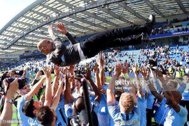 Manchester City players throw Josep Guardiola Manager of Manchester City in the air as they celebrate winning the Premier League title following the...