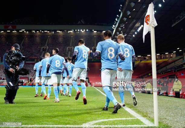 Manchester City players walk out wearing retro shirts with the number 8 in memory of Colin Bell during the Carabao Cup Semi Final match between...