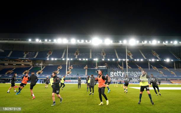 Manchester City players warm up prior to the Premier League match between Everton and Manchester City at Goodison Park on February 17, 2021 in...