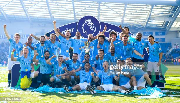 Manchester City pose with the Premier League trophy after the Premier League match between Brighton & Hove Albion and Manchester City at American...