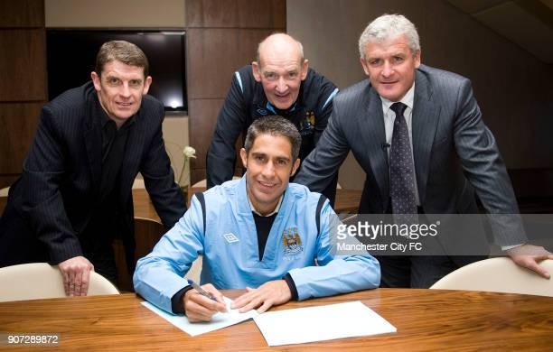 Manchester City Press Conference City of Manchester Stadium Manchester City's new signing Sylvinho signs his contract watched by Football...