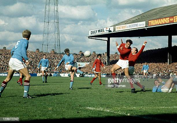 Manchester City striker Bobby Owen shoots as Manchester United defenders David Sadler and Nobby Stiles attempt to block his shot watched by George...