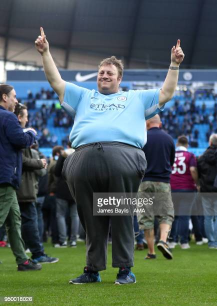 Manchester City supporter celebrates on the pitch after the Premier League match between Manchester City and Swansea City at Etihad Stadium on April...