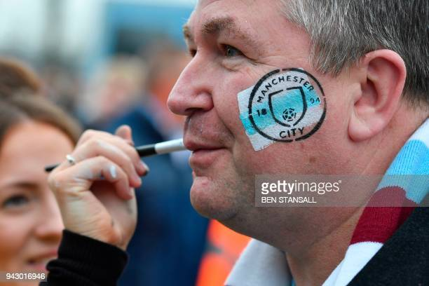 A Manchester City supporter gets a logo painted and stamped on his face outside the stadium ahead of the English Premier League football match...