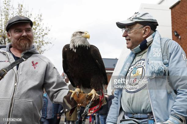 A Manchester City supporter is introduced to Crystal Palace mascot Kayla the Bald Eagle before the English Premier League football match between...