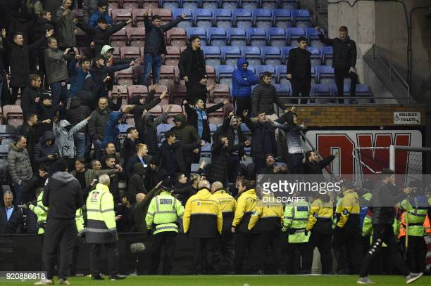 Manchester City supporters react after the English FA Cup fifth round football match between Wigan Athletic and Manchester City at the DW Stadium in...