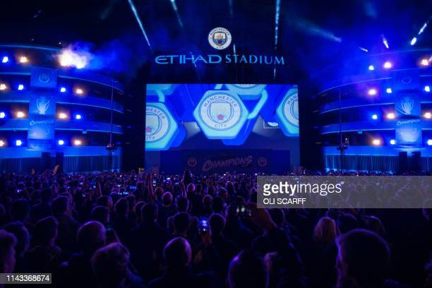 Manchester City supporters wait for players and coaching staff to arrive from Brighton to celebrate with the Premier League trophy outside the Etihad...