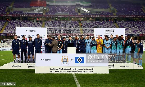 Manchester City team poses with the trophy after the friendly match between Hamburg SV and Manchester City at Hazza bin Zayed Stadium on January 21...