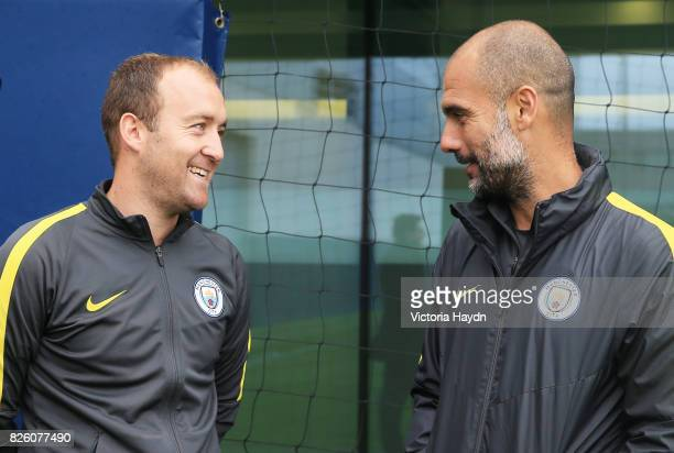 Manchester City Women's Nick Cushing is congratulated by Pep Guardiola at training