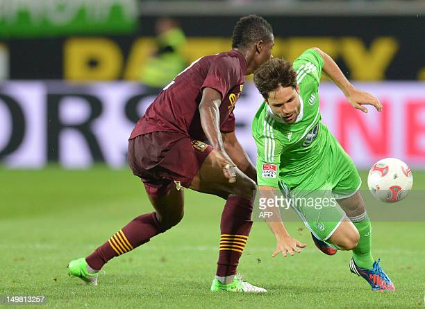 Manchester City's Abdul Razak vies for the ball with Wolfsburg's Brazilian midfielder Diego during the preseason friendly football match between VfL...