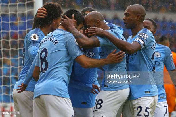 Manchester City's Algerian midfielder Riyad Mahrez celebrates with teammates after scoring their fourth goal during the English Premier League...