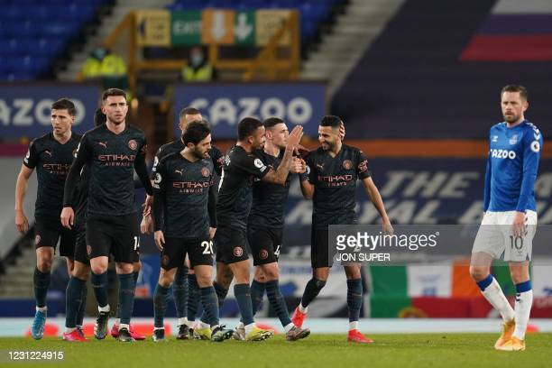 Manchester City's Algerian midfielder Riyad Mahrez celebrates with teammates after scoring his team's second goal during the English Premier League...