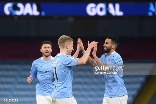 Manchester City's Algerian midfielder Riyad Mahrez celebrates with teammates after scoring his team's fourth goal during the English Premier League...