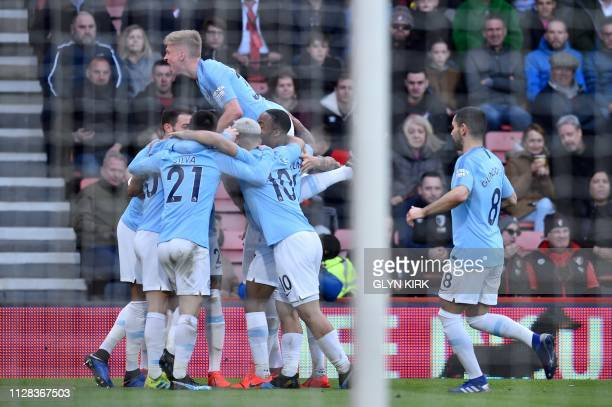 Manchester City's Algerian midfielder Riyad Mahrez is mobbed by teammates after scoring the opening goal during the English Premier League football...