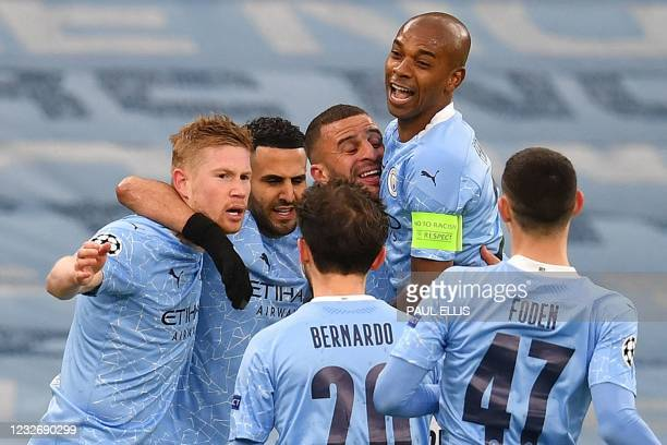 Manchester City's Algerian midfielder Riyad Mahrez is mobbed by teammates after scoring the opening goal during the UEFA Champions League second leg...