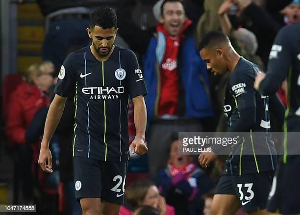 Manchester City's Algerian midfielder Riyad Mahrez passes Manchester City's Brazilian striker Gabriel Jesus as he reacts after failing to convert a...