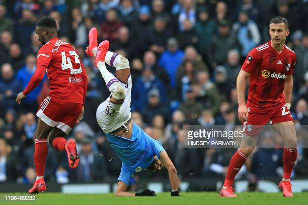 Manchester City's Algerian midfielder Riyad Mahrez takes a tumble during the English FA Cup fourth round football match between Manchester City and...