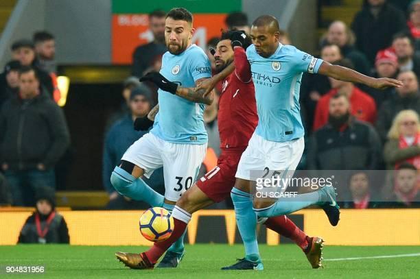 Manchester City's Argentinian defender Nicolas Otamendi and Manchester City's Brazilian midfielder Fernandinho try to stop Liverpool's Egyptian...