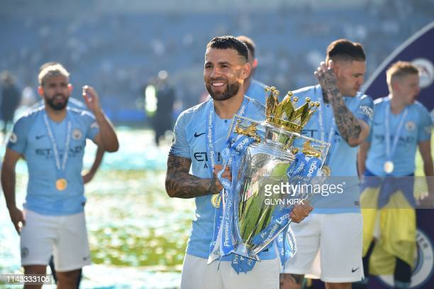 Manchester City's Argentinian defender Nicolas Otamendi poses with the Premier League trophy after their 41 victory in the English Premier League...