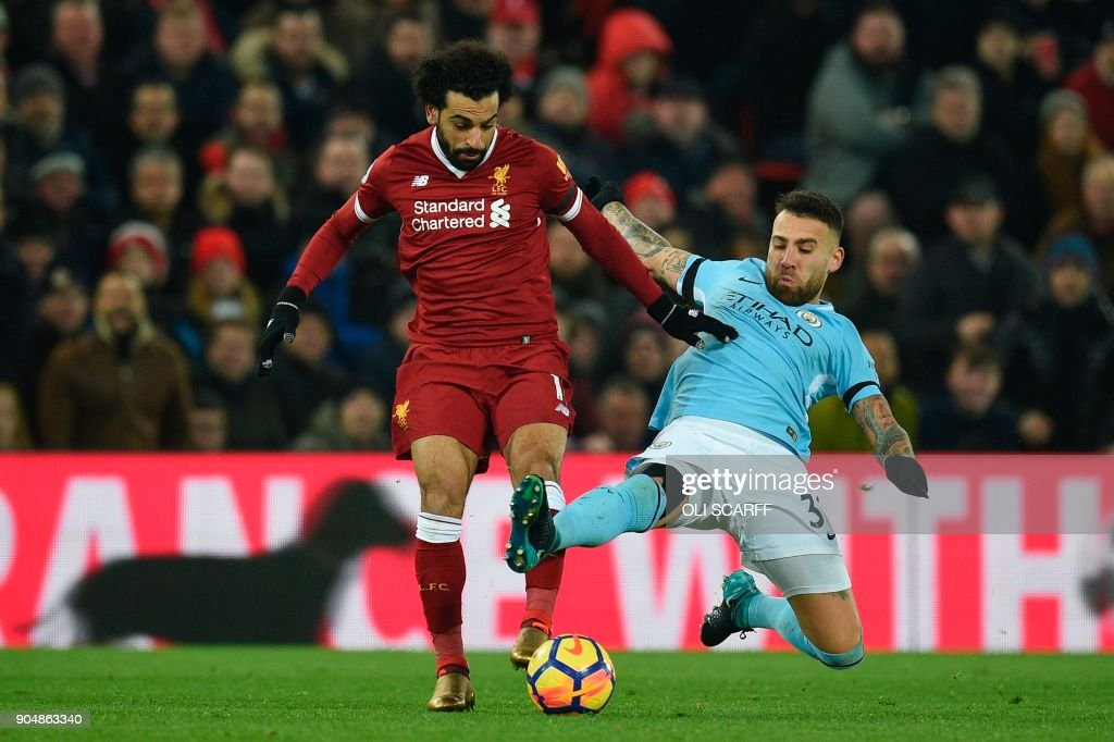 Manchester City's Argentinian defender Nicolas Otamendi (R) tries to tackle Liverpool's Egyptian midfielder Mohamed Salah (L) during the English Premier League football match between Liverpool and Manchester City at Anfield in Liverpool, north west England on January 14, 2018. / AFP PHOTO / Oli SCARFF / RESTRICTED TO EDITORIAL USE. No use with unauthorized audio, video, data, fixture lists, club/league logos or 'live' services. Online in-match use limited to 75 images, no video emulation. No use in betting, games or single club/league/player publications. /
