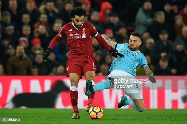 Manchester City's Argentinian defender Nicolas Otamendi tries to tackle Liverpool's Egyptian midfielder Mohamed Salah during the English Premier...