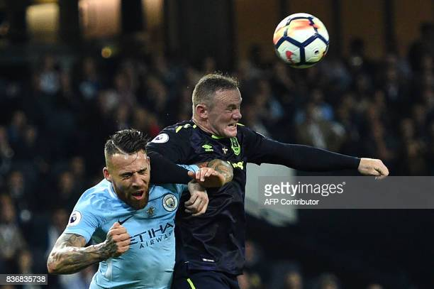 Manchester City's Argentinian defender Nicolas Otamendi vies with Everton's English striker Wayne Rooney during the English Premier League football...