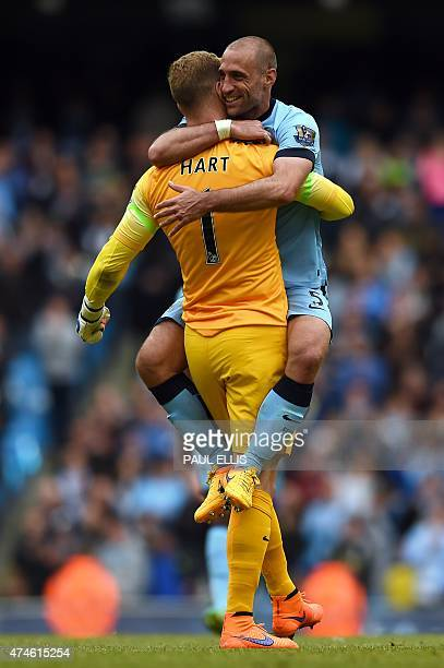 Manchester City's Argentinian defender Pablo Zabaleta jumps into the arms of Manchester City's English goalkeeper Joe Hart after the final whistle in...