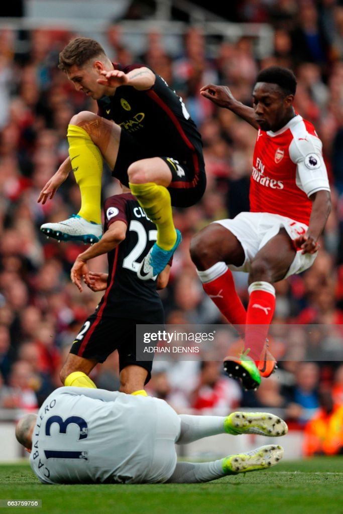Manchester CIty's Argentinian goalkeeper Willy Caballero saves at the feet of Arsenal's English striker Danny Welbeck (R) as Manchester City's English defender John Stones hurdles his goalkeeper during the English Premier League football match between Arsenal and Manchester City at the Emirates Stadium in London on April 2, 2017. / AFP PHOTO / Adrian DENNIS / RESTRICTED TO EDITORIAL USE. No use with unauthorized audio, video, data, fixture lists, club/league logos or 'live' services. Online in-match use limited to 75 images, no video emulation. No use in betting, games or single club/league/player publications. /
