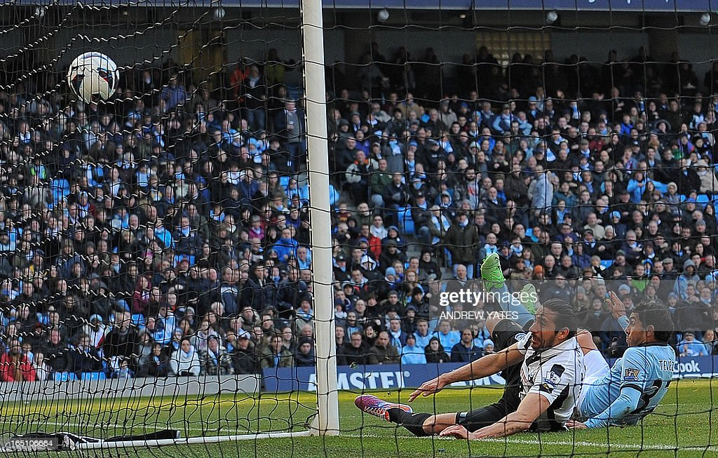 """Manchester City's Argentinian striker Carlos Tevez (R) scores the opening goal of the English Premier League football match between Manchester City and Newcastle United at the Etihad Stadium in Manchester, northwest England, on March 30, 2013. USE. No use with unauthorized audio, video, data, fixture lists, club/league logos or """"live"""" services. Online in-match use limited to 45 images, no video emulation. No use in betting, games or single club/league/player publications. """""""