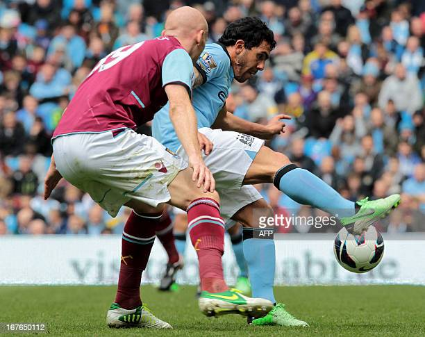 Manchester City's Argentinian striker Carlos Tevez tackles West Ham United's Welsh defender James Collins during the English Premier League football...