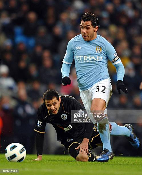 Manchester City's Argentinian striker Carlos Tevez vies with Wigan Athletic's Paraguayan defender Antolin Alcaraz during the English Premier League...