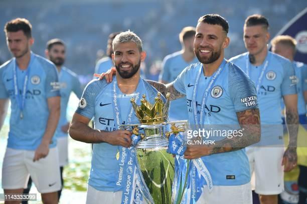 Manchester City's Argentinian striker Sergio Aguero and Manchester City's Argentinian defender Nicolas Otamendi pose with the Premier League trophy...