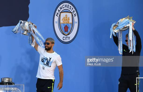 Manchester City's Argentinian striker Sergio Aguero and Manchester City's Belgian midfielder Kevin De Bruyne carry the League Cup and Premiere League...
