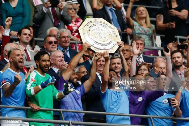 TOPSHOT Manchester City's Argentinian striker Sergio Aguero and Manchester City's Spanish midfielder David Silva raise the trophy after winning the...