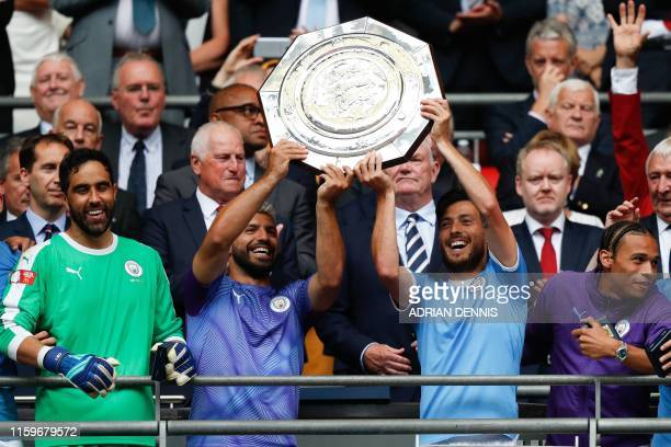 Manchester City's Argentinian striker Sergio Aguero and Manchester City's Spanish midfielder David Silva raise the trophy after winning the English...