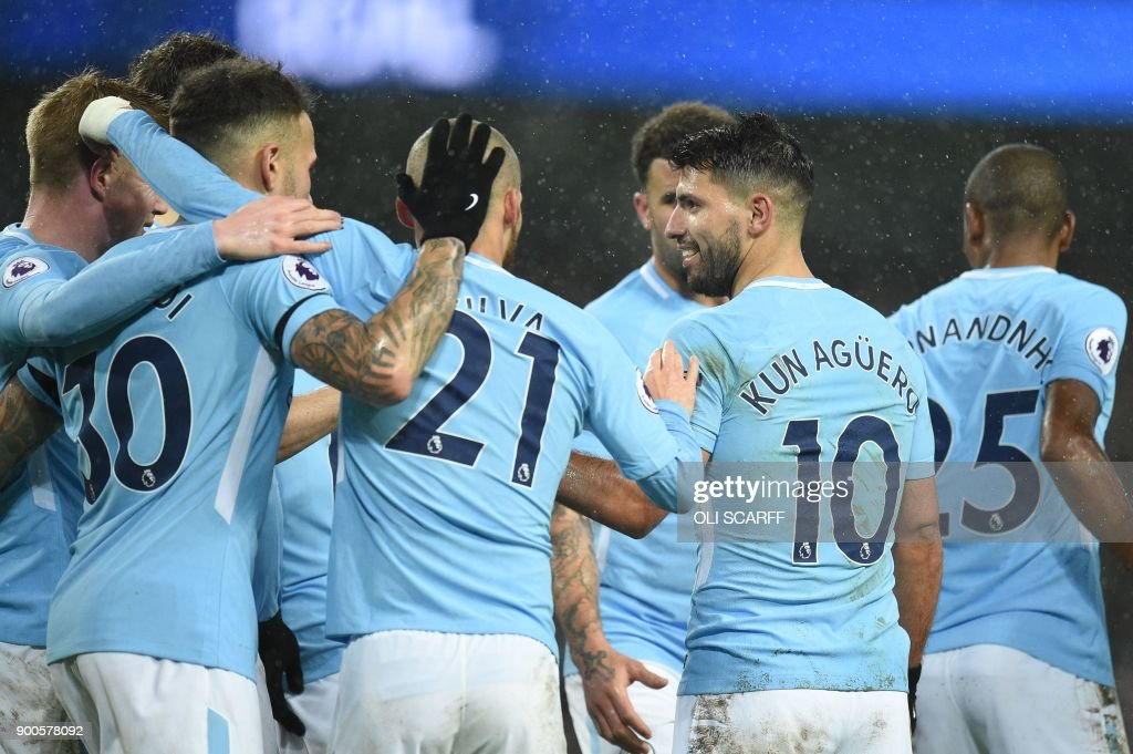 Manchester City's Argentinian striker Sergio Aguero (2R) celebrates after scoring their third goal with teammates during the English Premier League football match between Manchester City and Watford at the Etihad Stadium in Manchester, north west England, on January 2, 2018. / AFP PHOTO / Oli SCARFF / RESTRICTED TO EDITORIAL USE. No use with unauthorized audio, video, data, fixture lists, club/league logos or 'live' services. Online in-match use limited to 75 images, no video emulation. No use in betting, games or single club/league/player publications. /