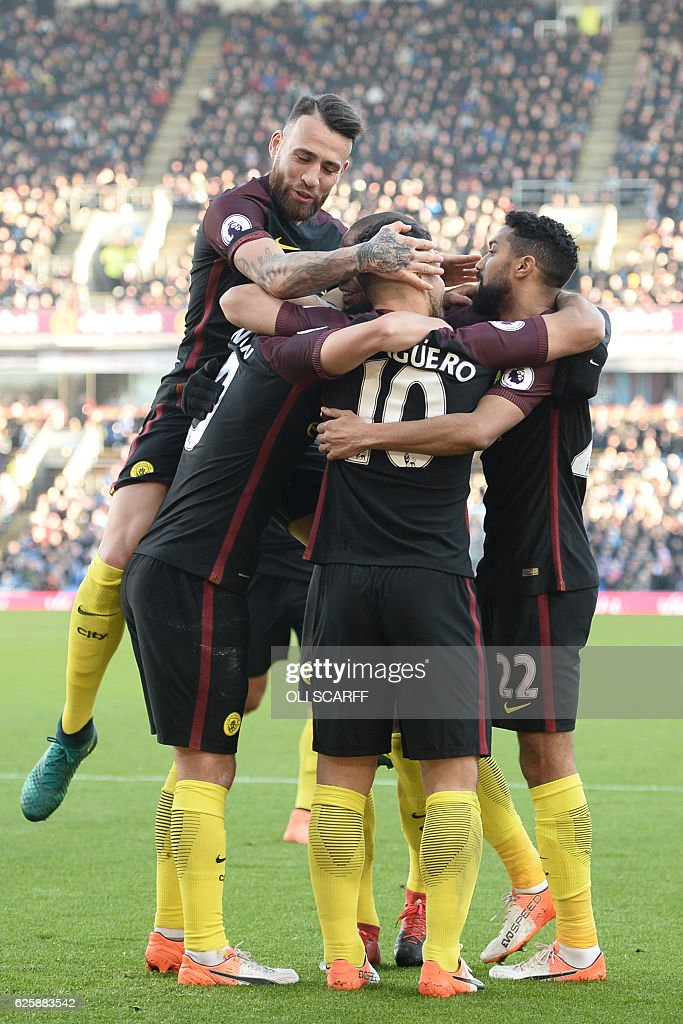 Manchester City's Argentinian striker Sergio Aguero (C) celebrates with teammates after scoring their second goal during the English Premier League football match between Burnley and Manchester City at Turf Moor in Burnley, north west England on November 26, 2016. / AFP / Oli SCARFF / RESTRICTED TO EDITORIAL USE. No use with unauthorized audio, video, data, fixture lists, club/league logos or 'live' services. Online in-match use limited to 75 images, no video emulation. No use in betting, games or single club/league/player publications. /