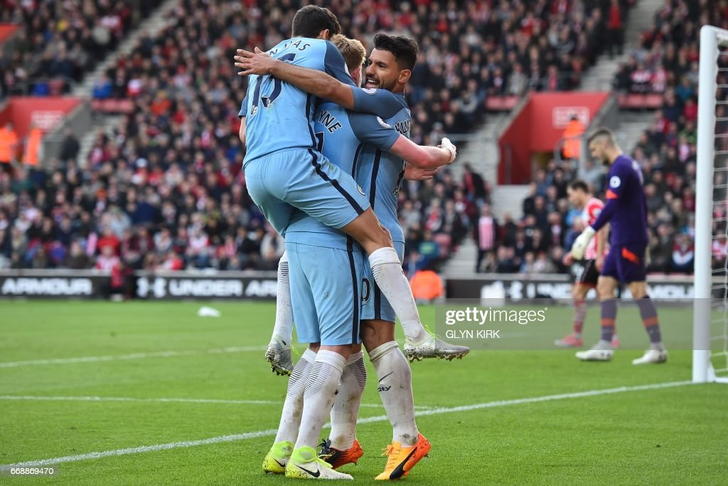 Manchester City's Argentinian striker Sergio Aguero (R) celebrates with teammates after scoring their third goal during the English Premier League football match between Southampton and Manchester City at St Mary's Stadium in Southampton, southern England on April 15, 2017. Manchester City won the game 3-0. / AFP PHOTO / Glyn KIRK / RESTRICTED TO EDITORIAL USE. No use with unauthorized audio, video, data, fixture lists, club/league logos or 'live' services. Online in-match use limited to 75 images, no video emulation. No use in betting, games or single club/league/player publications. /