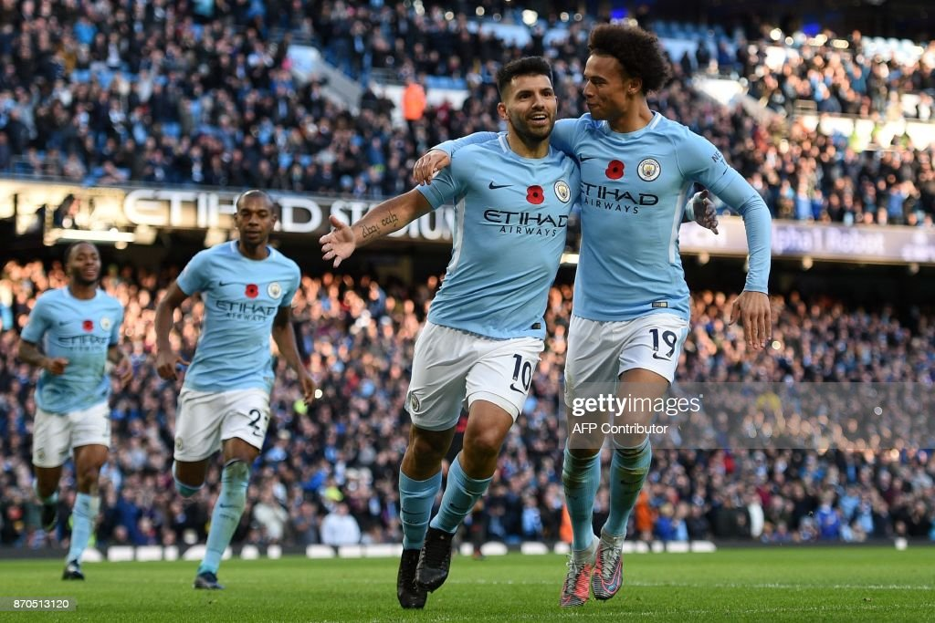 TOPSHOT - Manchester City's Argentinian striker Sergio Aguero (2nd R) celebrates with Manchester City's German midfielder Leroy Sane (R) after scoring their second goal from the penalty spot during the English Premier League football match between Manchester City and Arsenal at the Etihad Stadium in Manchester, north west England, on November 5, 2017. / AFP PHOTO / Oli SCARFF / RESTRICTED TO EDITORIAL USE. No use with unauthorized audio, video, data, fixture lists, club/league logos or 'live' services. Online in-match use limited to 75 images, no video emulation. No use in betting, games or single club/league/player publications. /